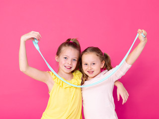 two beautiful girls playing with homemade slime and having a lot of fun in front of pink background