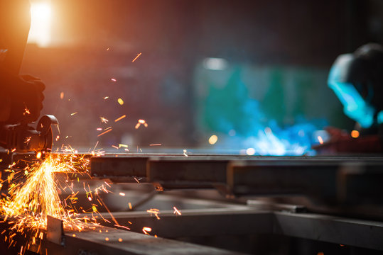 A man grinds metal. In the background a welder welds a part.