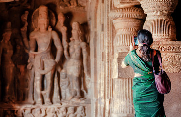 Woman making picture by iphone inside the 6th century Hindu temple with caves. Carvings in ancient places, India