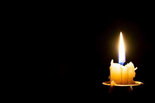 burning candle on a dark background and an empty black background on the left side