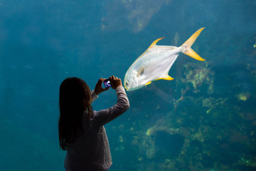 beautiful girl taking a picture in front of a giant aquarium