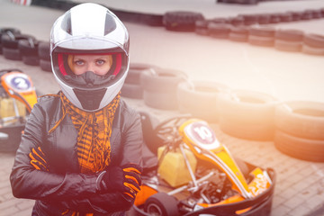 Portrait of a pretty girl wearing a white helmet close up, detail of Go-kart. karting track racing, copy space. serious look, determination, active lifestyle, extreme sport, soft light