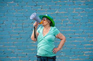 elderly grandmother in turquoise sweater and cowboy hat stands against gray brick wall