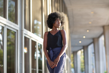 A young fashionable Afro-American woman confidently walking down the hall outside the financial building