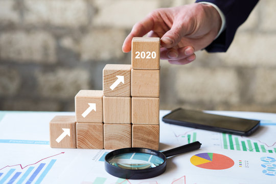 Business concept growth 2020 success process, Businessman hand arranging wood block stacking as step stair on paper chart closeup.