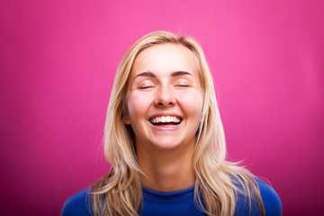 portrait of smiling young blond woman next to pink backdrop