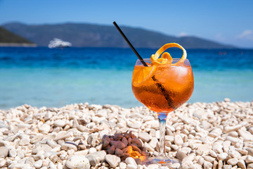 Glass of cold Aperol spritz cocktail on the white pebbles of the amazing Antisamos beach, Kefalonia island, Greece.
