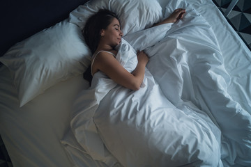 Young beautiful girl or woman sleeping alone in big bed at night, top view