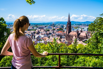 Germany, Beautiful young tourist girl standing above skyline of freiburg im breisgau city and famous muenster cathedral in summer surrounded by green trees