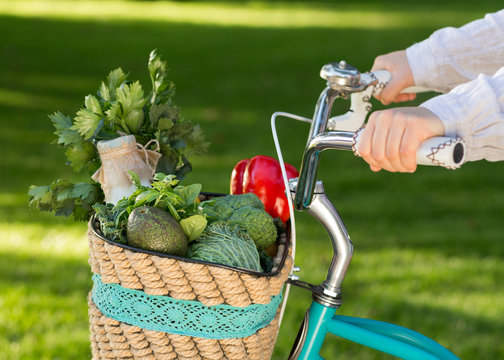 Woman ride a bike with full basket of fresh vegetables
