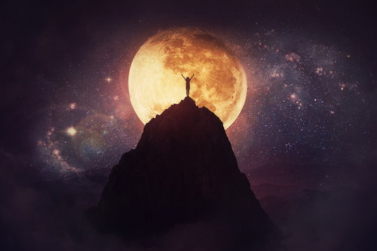 Self overcome concept as a person raising hands up on the top of a mountain over full moon night background. Conquering obstacles, success achieving. Road to win, freedom symbol.