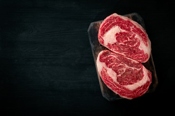 Ideal raw rib eye beef steak on black wooden background, top view and copy space