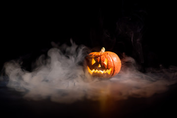 Halloween, orange pumpkin with a scary luminous face on a dark background. Gray thick smoke comes out.