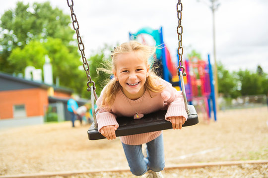 the girl on the playground swing on the school day