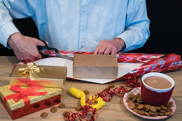 man wraps gift with red paper. For typical Dutch event called Sinterklaas