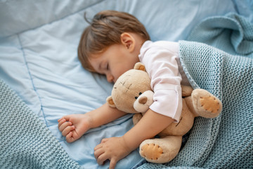 Sleepyhead. Young boy peacefully sleeping on a blue pillow. Baby needs his sleep! Baby boy sleeping with teddy bear and pacifier. Baby sleeping covered with soft blanket