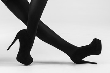 A woman's legs wearing black stockings and black stilletos.