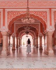 A woman walking through an ornate orange arched corridor.