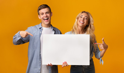 Young people holding blank advertising board and pointing on it