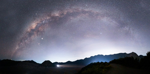 Beautiful night landscape with silhouette of Bromo mountain on the background Milky way galaxy - Bromo Tengger Semeru National Park , Indonesia