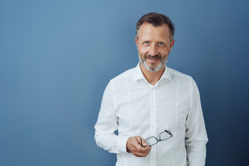 Friendly relaxed middle-aged man holding glasses