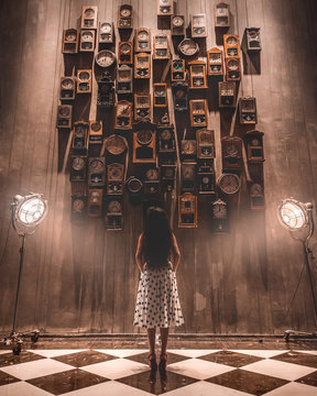 Woman in dress staring at a wall of clocks.