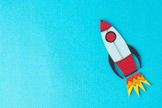 Start up business concept. Boost or increase incomes, salary. Drawn rocket on colorful blue background. Copy space.