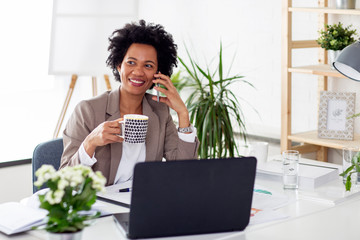 Woman using mobile phone while sitting at the desk in office with laptop in front of her