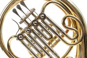 Corno, instrumento musical dorado sobre fondo blanco