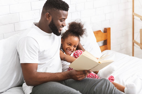 Loving african american dad reading fairy tales to his little daughter