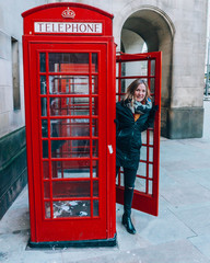 Smiling woman standing in traditional English red telephone booth