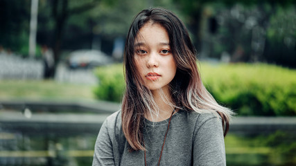 Portrait of Chinese Teenager. Asian Appearance. Calm, sad face. Cute Girl looking at the camera, a close up portrait in the park. Copy space.