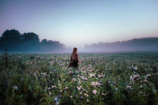 Woman standing in field of flowers