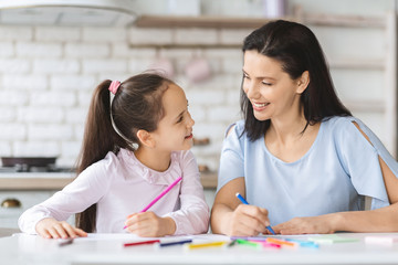 Cute daughter and young mother drawing together in kitchen
