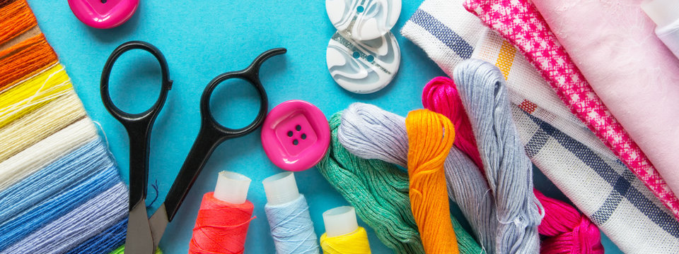Sewing flat lay, Composition with threads and sewing accessories on a blue background, flat lay, banner