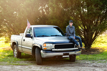 happy teenage boy from the south sitting on the front of his pickup truck outside in a rural area.