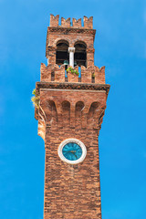 Historic architecture San Stefano Church Bell Tower with clock in Murano island, famous by glass making, Italy, Venice, against bright blue sky