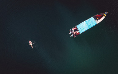 Aerial view of woman swimming in lake near boat