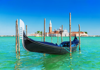 Venice seascape with gondola at wooden bricole mooring against famous San Giorgio Maggiore island and church in sunny day. View from from Piazza San Marco, Italy, Europe