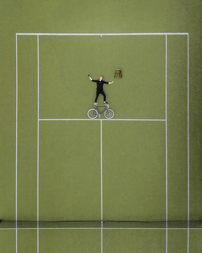 Aerial view of man with bicycle lying on tennis court