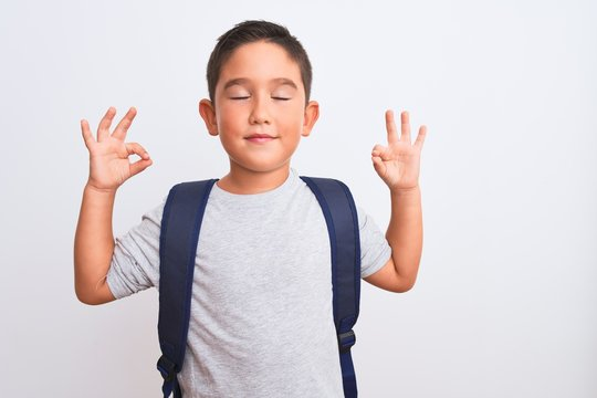 Beautiful student kid boy wearing backpack standing over isolated white background relax and smiling with eyes closed doing meditation gesture with fingers. Yoga concept.