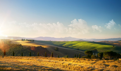 sunset over autumn Tuscany countryside landscape; rolling hills and village Wall mural