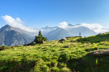 Fototapete - Wanderer in den Alpen mit wolkenverhangenen Bergen im Zillertal