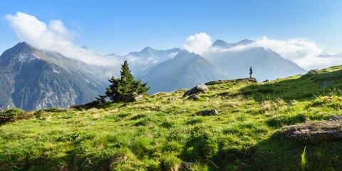 Wall Mural - Wanderer in den Alpen mit wolkenverhangenen Bergen als Panorama im Hintergrund