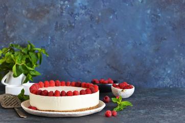 Vanilla cheesecake with raspberries on a stone background. New York cheesecake with raspberries.