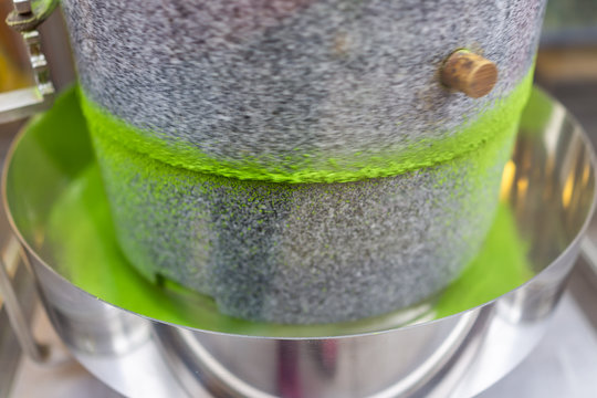 Matcha green tea grinding stone machine in motion with vibrant colorful powder in factory or tea shop