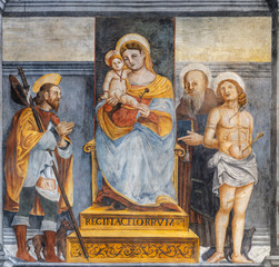Fototapete - LIMONE SUL GARDA, ITALY - MAY 9, 2015: The freso of Madonna with the saints Roch, Sebastian and probably Benedict in the church San Rocco.