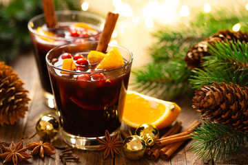 Christmas mulled red wine with spices, cranberry and oranges. Traditional hot drink or beverage,...