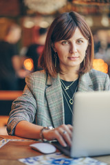 Portrait of a young business woman in gray blazer  sitting at table in cafe and working on net-book.  Freelancer working in coffee shop.