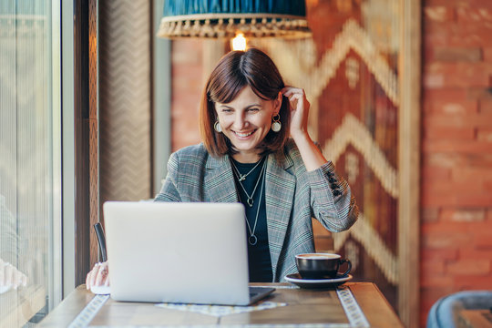 Young woman in  blazer with laptop  in the cafe near the window. Professions is a blogger, freelancer and writer. Freelancer working in coffee shop. Learning online..